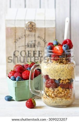 Healthy breakfast. Homemade granola, chia seeds yogurt and fresh berries in mason jar. - stock photo