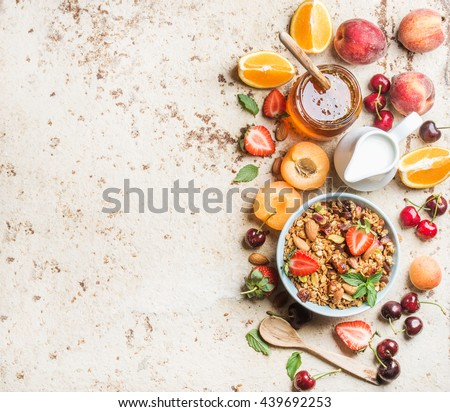Healthy breakfast ingredients. Bowl of oat granola with milk, fresh fruit, berries and honey. Top view, copy space - stock photo