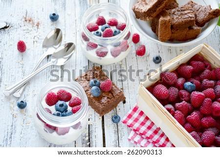 Healthy breakfast: jars with yogurt, fresh blueberries, raspberries and brownie cake on white table. High angle view - stock photo
