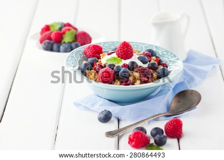 Healthy breakfast - muesli, milk and fresh berries on white wooden background, selective focus, health and diet concept - stock photo
