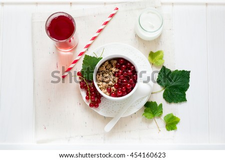 Healthy breakfast: muesli with yogurt and fresh berries in a bowl and juice on white wooden background - stock photo