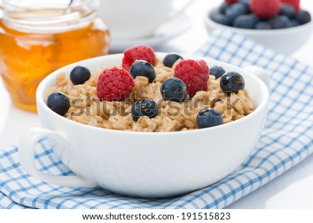 healthy breakfast - oat porridge with berries and honey, close-up - stock photo