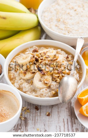 healthy breakfast - oatmeal with banana, honey and walnuts, vertical, top view - stock photo
