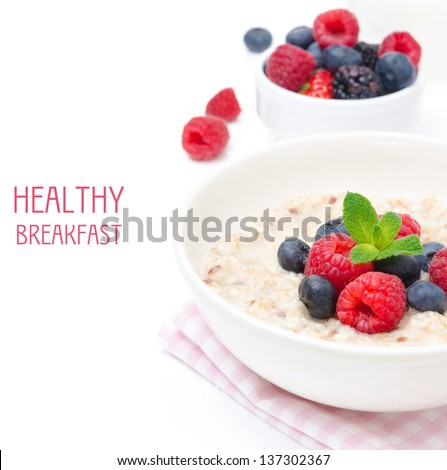healthy breakfast - oatmeal with fresh berries in a bowl isolated on white, fresh berries in the background - stock photo