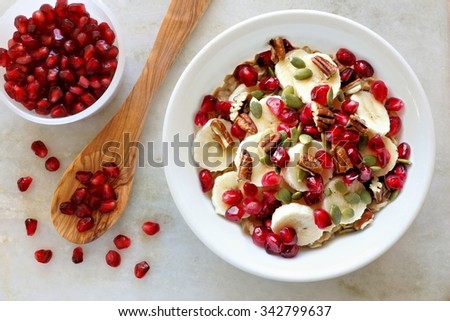 Healthy breakfast oatmeal with pomegranate, bananas, seeds and nuts, overhead scene on white marble                  - stock photo