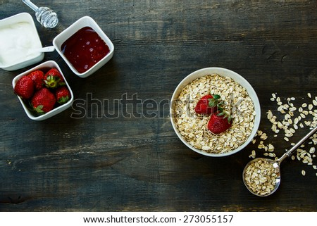 Healthy Breakfast. Oats and berries over dark vintage wood. Health and diet concept. Top view. - stock photo