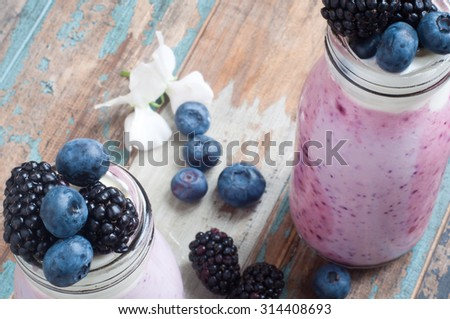 Healthy breakfast of a mixed berry smoothie milkshake made from blended blueberries and blackberries  with yogurt. Served in a glass bottle on a rustic wooden table. - stock photo