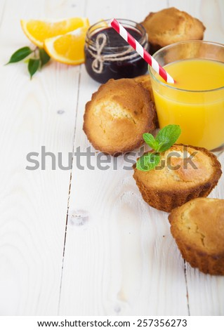 Healthy breakfast of muffins, juice, oranges and jam on a wooden background - stock photo
