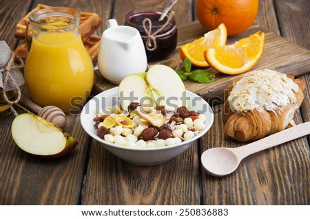 Healthy breakfast of oatmeal, croissants, apples, fresh juice, jam and oranges on a wooden background - stock photo