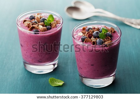 Healthy breakfast of smoothie, dessert, yogurt or milkshake with frozen blueberry and oats decorated grated chocolate and mint leaves on wooden rustic table - stock photo