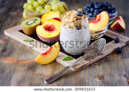 Healthy breakfast or morning snack with chia seeds pudding, granola, fruits and berries, vegetarian food, diet and health concept - stock photo