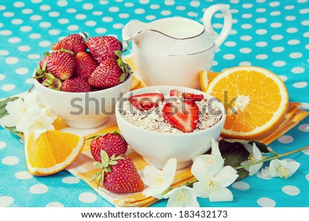 Healthy breakfast. Rolled oats, strawberries and oranges in a beautiful tablecloth.Vintage retro hipster style version - stock photo