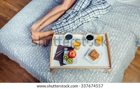 Healthy breakfast served on a wooden tray ready to eat beside of couple legs over a bed. Healthy food and home lifestyle concept. - stock photo