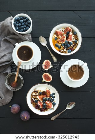Healthy breakfast set. Bowls of oat granola with yogurt, fresh blueberries and figs, coffee, honey, over black wooden backdrop. Top view - stock photo