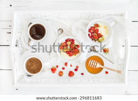 Healthy breakfast set. Yogurt and wild strawberry bowls with honey and black coffee on serving tray over white rustic wooden backdrop, top view - stock photo