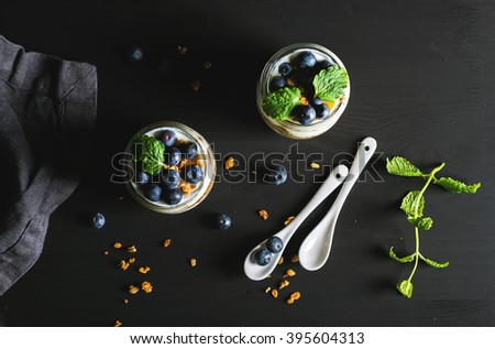 Healthy breakfast set. Yogurt oat granola with blueberries and mint leaves in glass jars on black backdrop, top view - stock photo