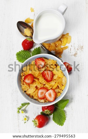 Healthy Breakfast with corn flakes, milk and strawberry on old wooden background. Health and diet concept - stock photo