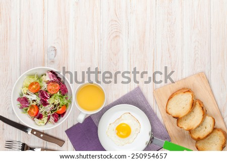 Healthy breakfast with fried egg, toasts and salad on white wooden table with copy space  - stock photo