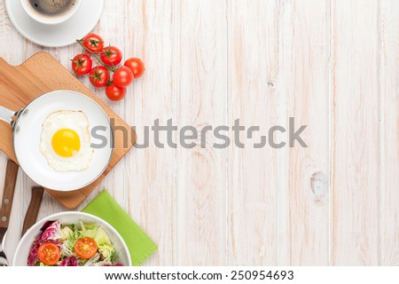 Healthy breakfast with fried egg, tomatoes and salad on white wooden table with copy space  - stock photo