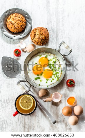 Healthy breakfast with fried eggs in a frying pan on a white table - stock photo