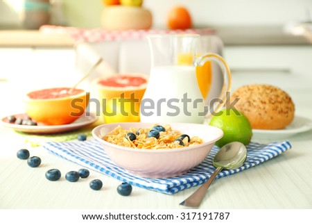Healthy breakfast with fruits and berries on table in kitchen - stock photo