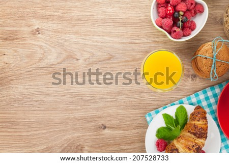 Healthy breakfast with muesli, berries, orange juice, coffee and croissant. View from above on wooden table with copy space - stock photo