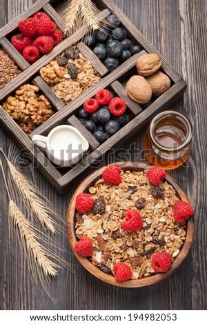 Healthy breakfast with muesli, granola. Honey, nuts, blueberries, raspberries, milk.  - stock photo