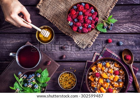 Healthy breakfast with pumpkin porridge, berries and herbal tea with honey at village summer house - stock photo