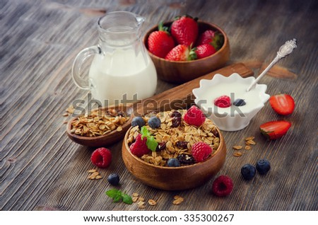 Healthy breakfast with rolled oats and berries in wooden bowls, granola or muesli - stock photo