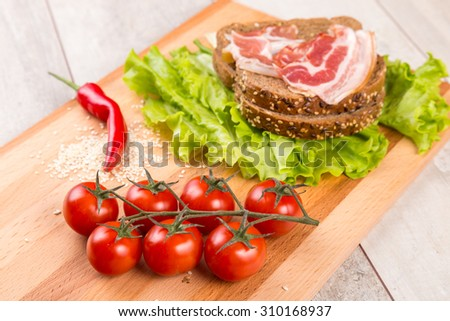 Healthy breakfast with tomato, toasts, meat and salad on wooden table. - stock photo
