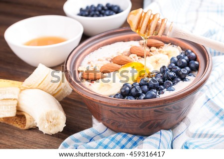 Healthy breakfast with yogurt, fruits, nuts and berries. Smoothie bowl with banana, blueberries, almond and honey - stock photo