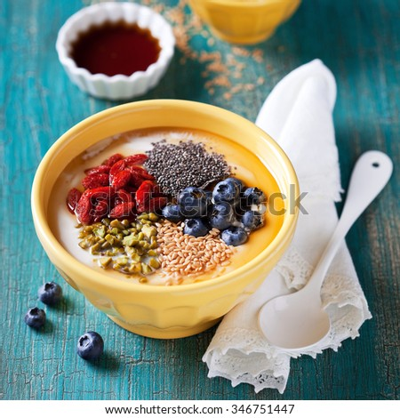 Healthy breakfast yogurt bowl with chia seeds, flax seeds, goji berries, blueberries, pistachio and maple syrup, selective focus - stock photo