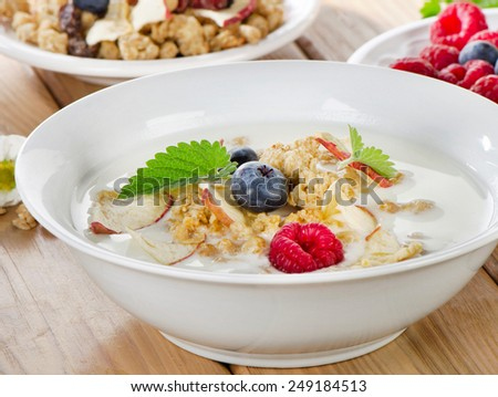 Healthy breakfast - yogurt with muesli and berries. Selective focus - stock photo