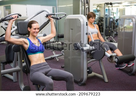 Healthy brunette using weights machine for arms at the gym - stock photo