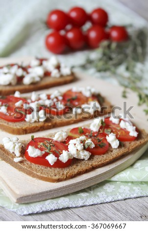 Healthy bruschetta with rye bread, cherry tomatoes, feta cheese and thyme, selective focus - stock photo
