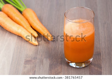 Healthy carrot smoothie in a glass and raw carrots on a wooden background - stock photo