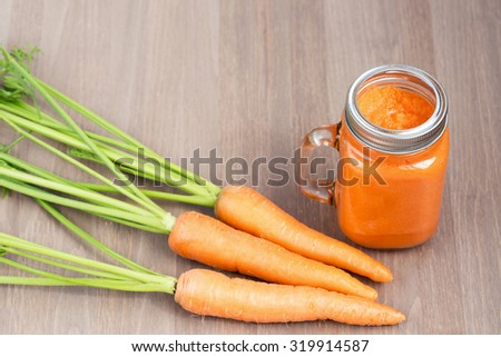Healthy carrot smoothie in a jar with carrots on wooden background. Shallow dof - stock photo