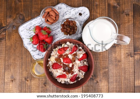 Healthy cereal with milk and strawberry on wooden table - stock photo