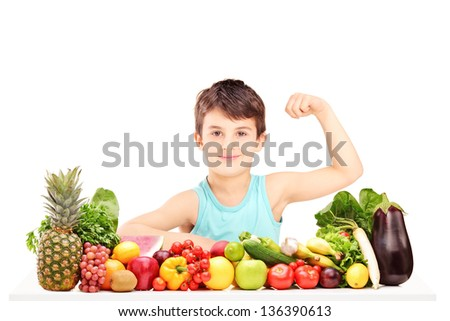 Healthy child showing his arm muscles and sitting on a table full of pile of fruits and vegetables - stock photo