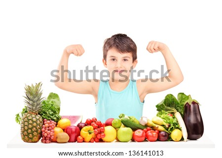 Healthy child showing his muscles and sitting on a table full of pile of food isolated on white background - stock photo