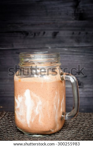 Healthy chocolate flavor smoothie milkshake made from blended cacau,chia with yoghurt swirl. Served in a jug style glass with nut topping.  - stock photo