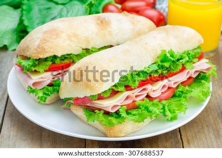 Healthy ciabatta bread sandwiches with ham and cheese on the white plate  - stock photo