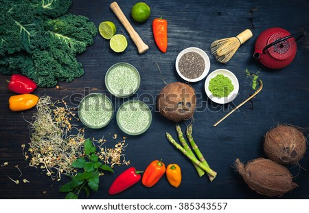 Healthy Clean eating food concept - matcha green tea, cocnut milk, vegetables smoothie bowls with superfood ingredients, top view, dark wooden table, rustic style - stock photo