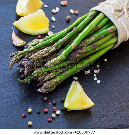 Healthy concept. Bunch of organic fresh asparagus with ingredients for cooking on a grunge stone table. Selective focus - stock photo