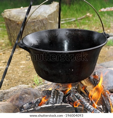 healthy cooking on ancient traditional big metal pot ( vintage black cauldron ) on camp fire - stock photo