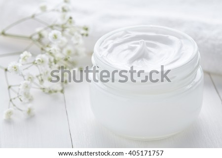 Healthy cosmetic cream with herbal flowers face care hygiene moisture lotion therapy in glass jar with towel on white background - stock photo