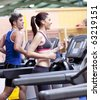 Healthy couple running on a treadmill in a sport centre - stock photo