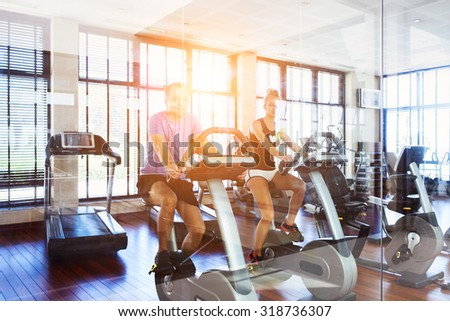 Healthy couple training on a treadmill in a sport center - stock photo