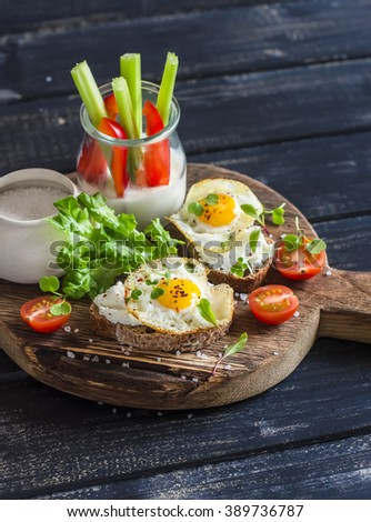 Healthy delicious breakfast or snack -  sandwich with cheese and a fried quail egg, greek yogurt, celery and sweet peppers on rustic wooden board - stock photo