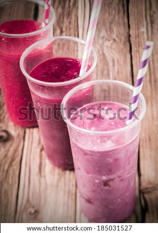 Healthy delicious trio of different berry smoothies with low fat yogurt arranged in a diagonal row, high angle view on an old rustic wooden background - stock photo